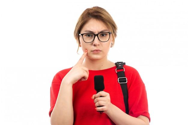 Uma vista frontal jovem aluna de camiseta vermelha, vestindo bolsa preta, segurando o microfone hesitando expressão no branco