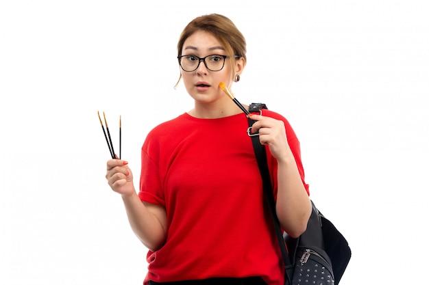Uma vista frontal jovem aluna em jeans t-shirt preto preto segurando pincéis no branco
