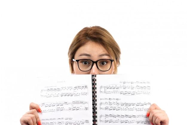Uma vista frontal jovem aluna em jeans vermelho de camiseta preta, usando fones de ouvido pretos, segurando o caderno de nota em branco