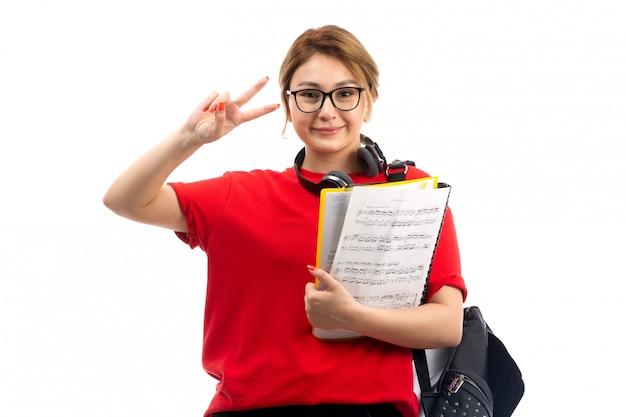 Uma vista frontal jovem aluna em jeans vermelho de camiseta preta, usando fones de ouvido pretos, segurando o caderno nota sorrindo no branco