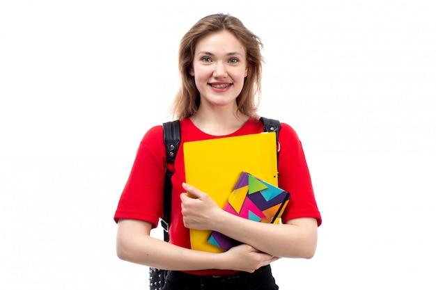 Uma vista frontal jovem aluna na bolsa vermelha camisa preta segurando arquivos de cadernos sorrindo em branco