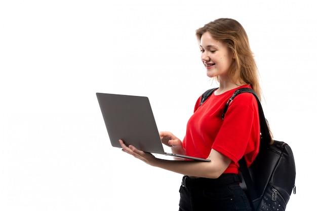 Uma vista frontal jovem aluna na bolsa vermelha camisa preta usando laptop no branco