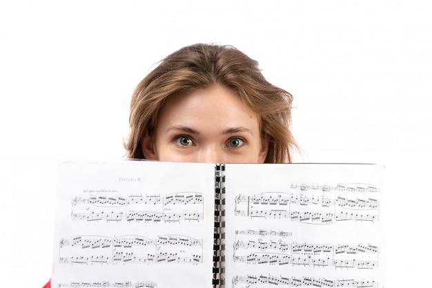 Uma vista frontal jovem aluna na camisa vermelha bolsa preta com fones de ouvido pretos sorrindo segurando o caderno em branco