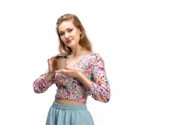 Uma vista frontal jovem atraente de camisa colorida e saia azul, segurando a xícara de café em branco