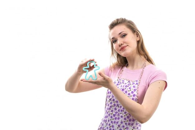 Uma vista frontal jovem atraente dona de casa na capa rosa camisa colorida posando sorrindo segurando pouco azul humano formado brinquedo sobre o fundo branco cozinha cozinha