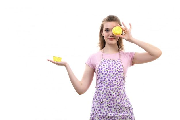 Uma vista frontal jovem atraente dona de casa na capa rosa camisa colorida segurando amarelo coisa sorrindo sobre o fundo branco cozinha cozinha fêmea