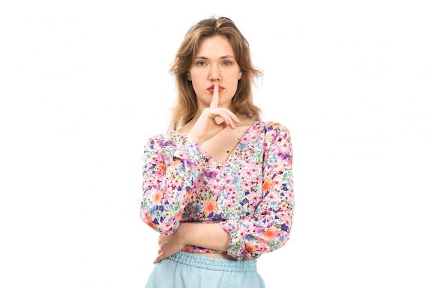Uma vista frontal jovem atraente em flor colorida projetada camisa e saia azul posando mostrando sinal de silêncio no branco