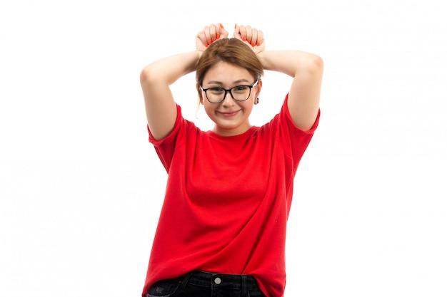 Uma vista frontal jovem atraente em t-shirt vermelha, vestindo jeans preto em óculos de sol posando sorrindo coquete no branco