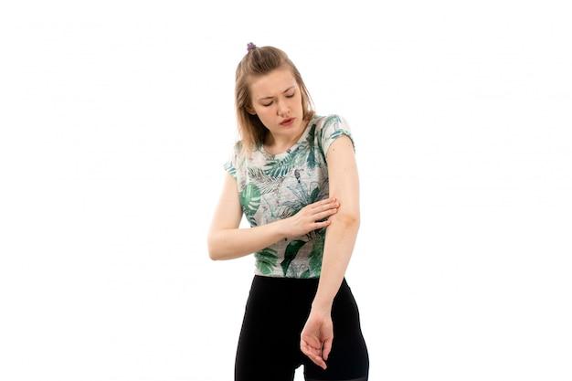 Uma vista frontal jovem atraente na camisa projetada e calça preta, sofrendo de dor no braço em branco