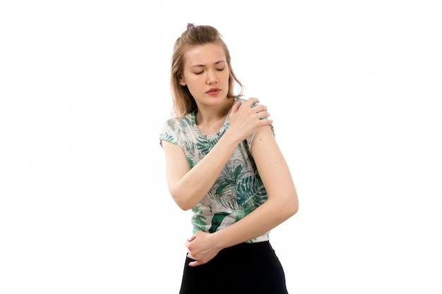 Uma vista frontal jovem atraente na camisa projetada e calça preta, sofrendo de dor no ombro em branco