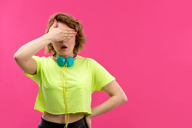 Uma vista frontal jovem bonita em calças de camisa colorida de ácido preto com fones de ouvido azuis cobrindo os olhos