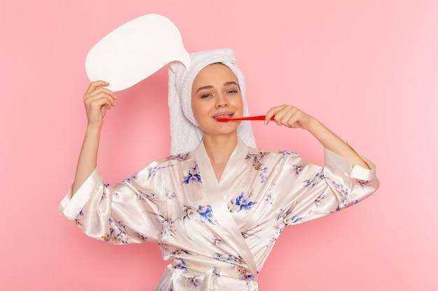 Uma vista frontal jovem bonita em roupão segurando placa branca e limpar os dentes
