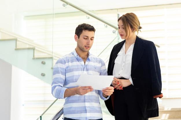 Uma vista frontal jovem bonito na camisa listrada, conversando e discutindo questões de trabalho com a jovem empresária durante a construção da atividade de trabalho diurno