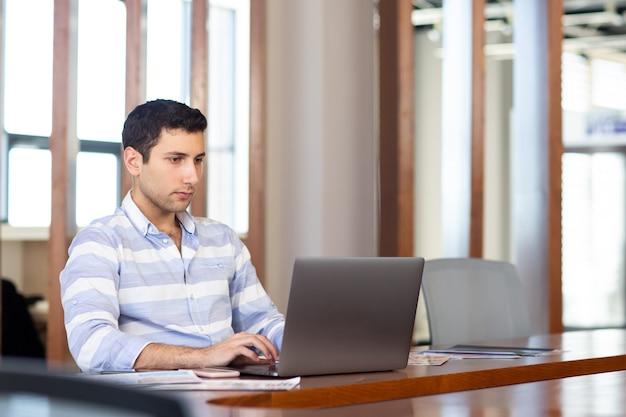 Uma vista frontal jovem bonito na camisa listrada, trabalhando dentro da sala de conferências, usando seu laptop prateado durante a atividade de trabalho diurno