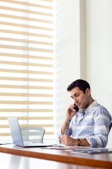 Uma vista frontal jovem bonito na camisa listrada, trabalhando dentro da sala de conferências, usando seu laptop prateado, olhando através de documentos falando ao telefone durante o dia de trabalho atividade edifício