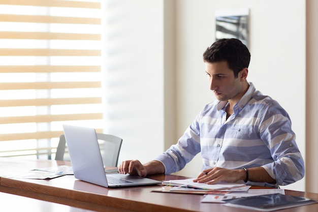 Uma vista frontal jovem bonito na camisa listrada, trabalhando dentro de seu escritório usando seu laptop prateado durante a atividade de trabalho durante o dia