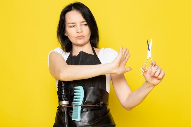 Uma vista frontal jovem cabeleireiro feminino na capa branca de camiseta preta, segurando a tesoura de cabelo expressão preocupada