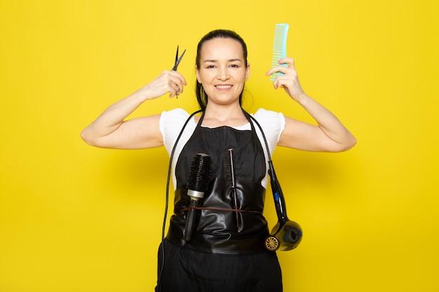 Uma vista frontal jovem cabeleireiro feminino na capa branca de camiseta preta, segurando uma tesoura e escova sorrindo posando