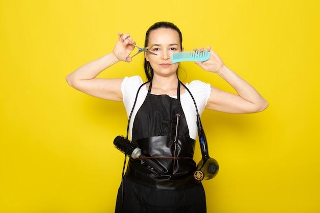 Uma vista frontal jovem cabeleireiro feminino na capa branca de camiseta preta, segurando uma tesoura escova posando