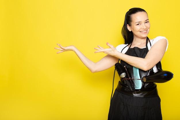 Uma vista frontal jovem cabeleireiro feminino na capa branca de camiseta preta sorrindo posando de boas-vindas