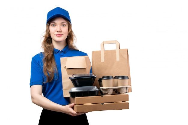 Uma vista frontal jovem correio feminino de boné azul camisa azul e calça preta segurando pacotes de entrega em branco