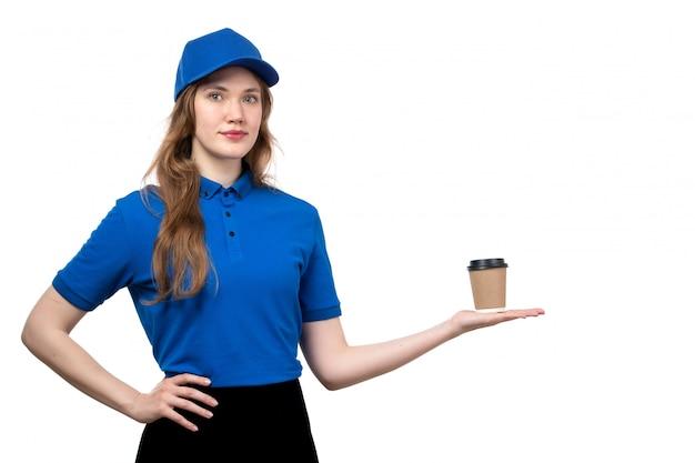 Uma vista frontal jovem correio feminino de camisa azul, boné azul e calça preta, segurando a xícara de café em branco