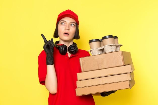 Uma vista frontal jovem correio feminino em luvas pretas uniformes vermelhas e boné vermelho segurando caixas de alimentos e copos de café