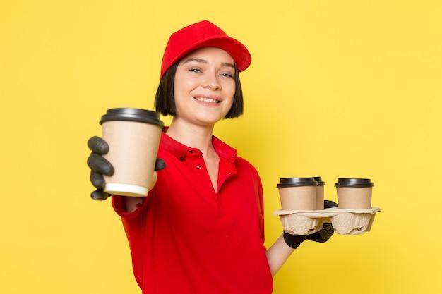 Uma vista frontal jovem correio feminino em luvas pretas uniformes vermelhas e boné vermelho segurando copos de café