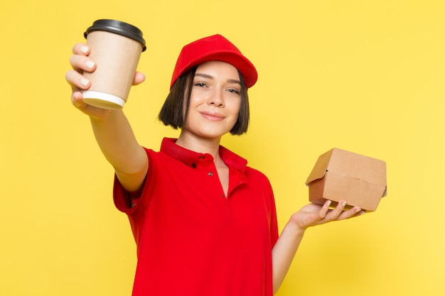 Uma vista frontal jovem correio feminino em luvas pretas uniformes vermelhas e boné vermelho segurando o pacote de alimentos e a xícara de café