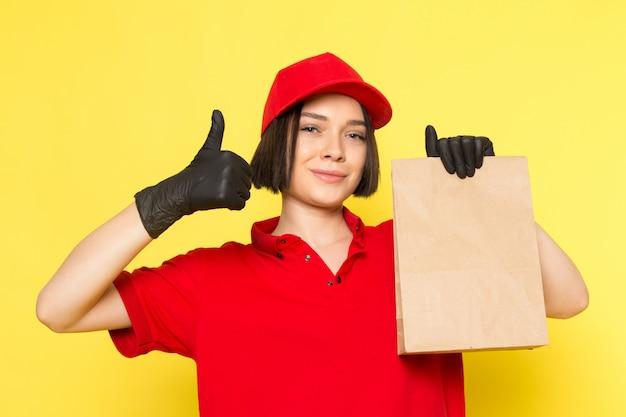 Uma vista frontal jovem correio feminino em luvas pretas uniformes vermelhas e boné vermelho segurando o pacote de alimentos
