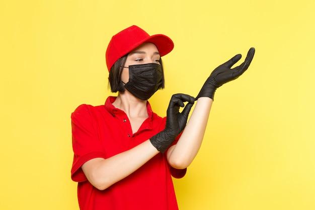 Uma vista frontal jovem correio feminino em luvas pretas uniformes vermelhas e boné vermelho usando suas luvas