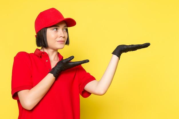 Uma vista frontal jovem correio feminino em luvas vermelhas uniformes pretas e boné vermelho posando