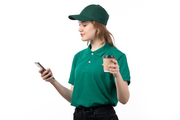 Uma vista frontal jovem correio feminino em uniforme verde segurando a xícara de café e usando um telefone em branco