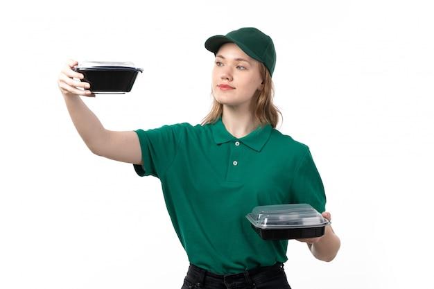 Uma vista frontal jovem correio feminino em uniforme verde segurando taças com comida sorrindo em branco