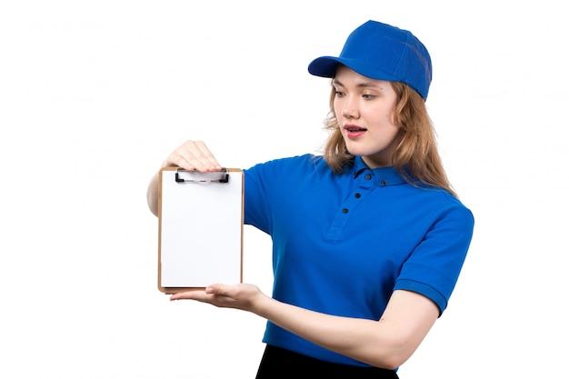 Uma vista frontal jovem correio feminino na camisa azul, boné azul e calça preta, segurando o bloco de notas em branco