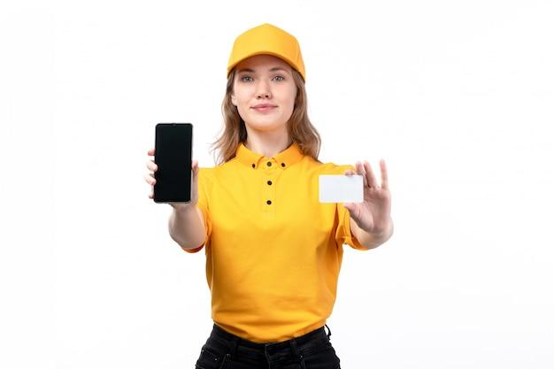 Uma vista frontal, jovem, correio feminino, trabalhadora, de, serviço entrega entrega, sorrindo, segurando, cartão branco, e, smartphone, branco