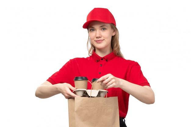 Uma vista frontal, jovem, correio feminino, trabalhadora, de, serviço entrega entrega, sorrindo, segurando, entrega, pacote, e, copos, com, café branco