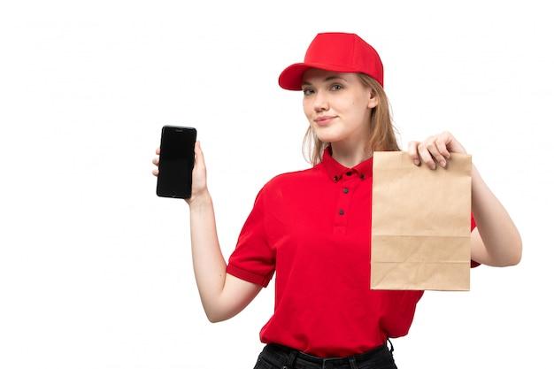 Uma vista frontal, jovem, correio feminino, trabalhadora, de, serviço entrega entrega, sorrindo, segurando, entrega, pacote entrega, e, smartphone, ligado