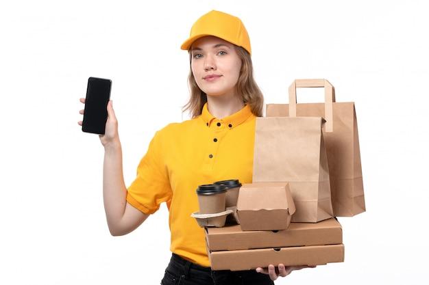 Uma vista frontal, jovem, correio feminino, trabalhadora, de, serviço entrega entrega, sorrindo, segurando, pacotes comida, e, copos café, junto, com, smartphone, branco