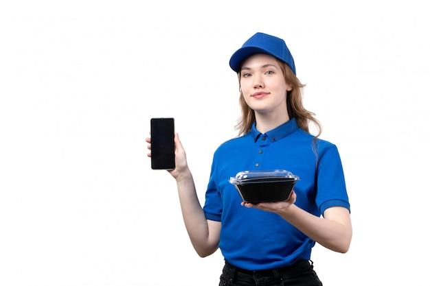 Uma vista frontal, jovem, correio feminino, trabalhadora, de, serviço entrega entrega, sorrindo, segurando, smartphone, e, tigela, com, alimento, branco