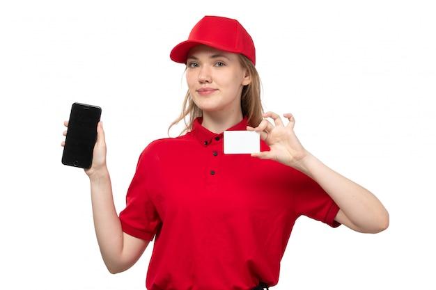 Uma vista frontal, jovem, correio feminino, trabalhadora, de, serviço entrega entrega, sorrindo, segurando, whtie, cartão, e, smartphone, branco