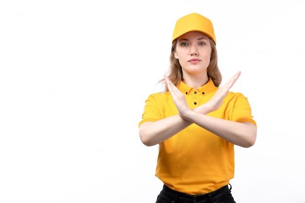Uma vista frontal jovem correio feminino trabalhadora do serviço de entrega de comida mostrando sinal de proibição posando em branco