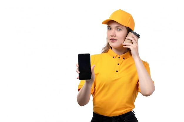 Uma vista frontal jovem correio feminino trabalhadora do serviço de entrega de comida segurando a xícara de café e smartphone em branco