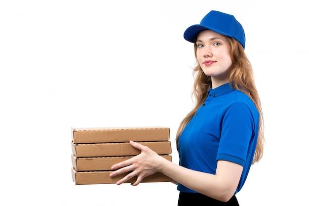 Uma vista frontal jovem correio feminino trabalhadora do serviço de entrega de comida segurando caixas de entrega de pizza em branco