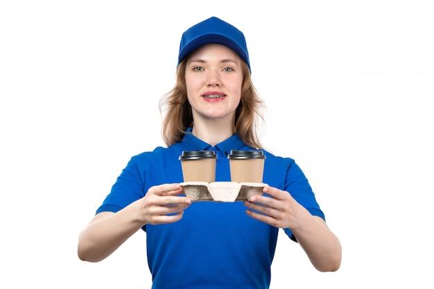 Uma vista frontal jovem correio feminino trabalhadora do serviço de entrega de comida segurando copos de café sorrindo em branco