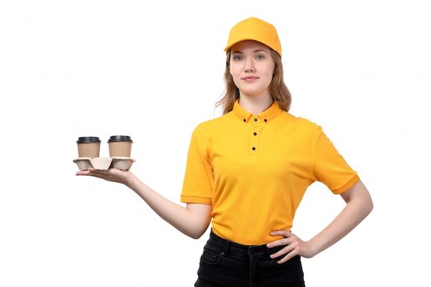Uma vista frontal jovem correio feminino trabalhadora do serviço de entrega de comida segurando copos de café sorrindo sobre fundo branco, entregando uniforme de serviço