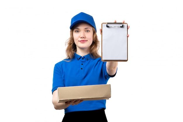 Uma vista frontal jovem correio feminino trabalhadora do serviço de entrega de comida segurando o pacote de alimentos e o bloco de notas em branco
