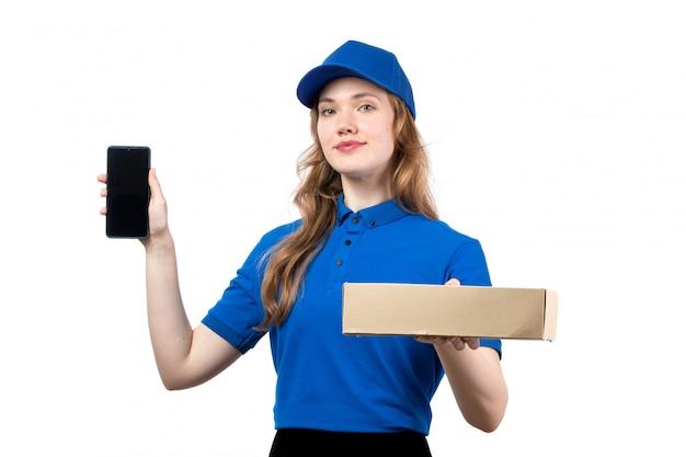 Uma vista frontal jovem correio feminino trabalhadora do serviço de entrega de comida segurando o pacote de entrega de comida e smartphone em branco