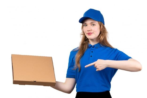 Uma vista frontal jovem correio feminino trabalhadora do serviço de entrega de comida segurando o pacote de entrega de comida sorrindo em branco