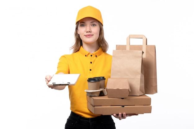 Uma vista frontal jovem correio feminino trabalhadora do serviço de entrega de comida sorrindo enquanto segura copos de café pacotes de comida em branco